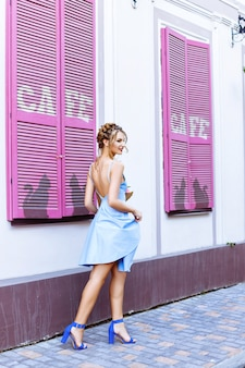 Beautiful girl in a blue dress posing on the street near a cafe with pink windows