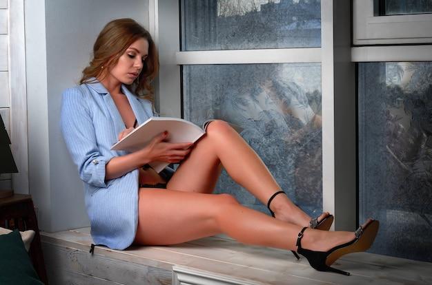 A beautiful girl in a blue jacket reads a magazine sitting on the windowsill near the frozen window.