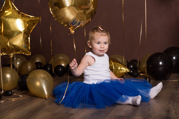 Beautiful girl in blue princess skirt with baloons