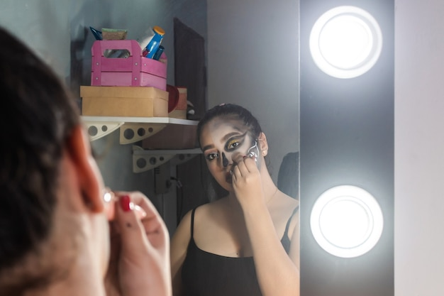 Beautiful girl blurring her halloween makeup from her face in her room.