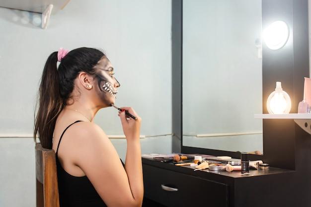 Beautiful girl blurring her halloween makeup in her room.