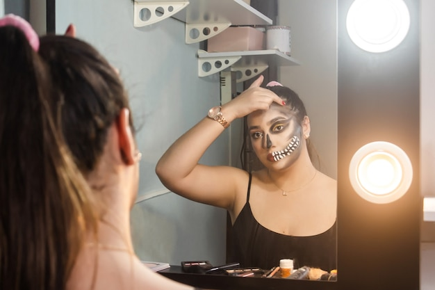 Beautiful girl blurring her makeup of an artistic skull for halloween in her room.