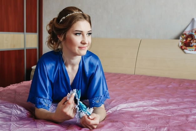 Beautiful girl, the bride in a dressing gown on the background of the apartment. wedding, bride's gathering, family creation.