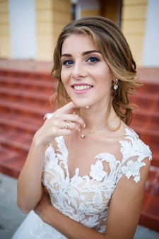 彼らの結婚式の日に柱のある大きな家の背景を歩く電車と白いドレスを着た美しい少女の花嫁