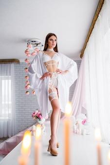 Красивая девушка невеста в белом кружевном будуарном платье, закрытом вуалью, в день свадьбы утром на красивом пейзаже цветов.