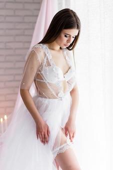 흰색 레이스 내실 드레스 린넨에 아름 다운 여자 신부는 꽃의 아름 다운 풍경에 결혼식 날 아침에 베일으로 마감했다.