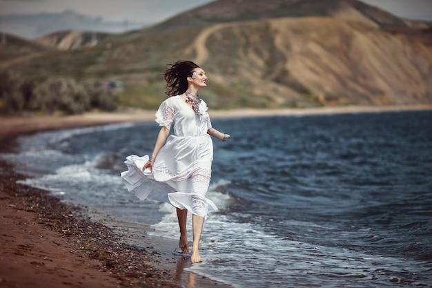 美しい少女、花嫁、白いドレスを着て、裸足で、ビーチ、水の上を走り、笑う