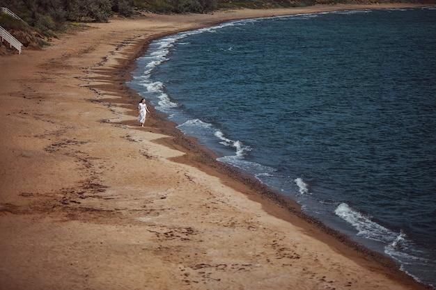 美しい少女、花嫁、白いドレスを着て、裸足で、水辺のビーチを歩く