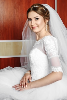 Beautiful girl, bride in a white dress on the background of the apartment. wedding, bride's gathering, family creation.