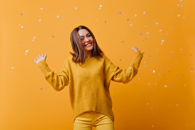 Beautiful girl in bright clothes dancing with pleasure. enthusiastic caucasian lady in yellow sweater fooling around during indoor photoshoot.