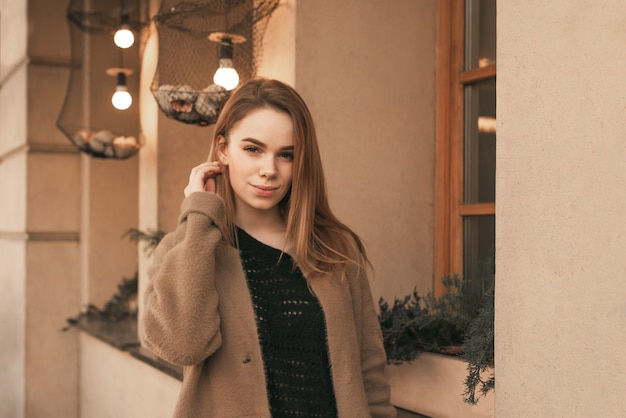 Beautiful girl in a brown coat poses on the camera near the brown wall, looks at the camera and smiles