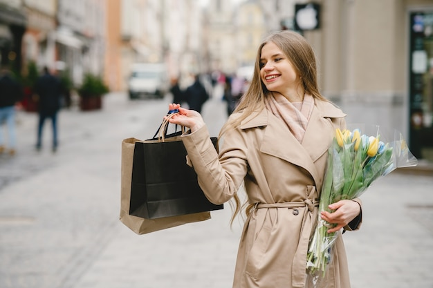 Beautiful girl in a brown coat. woman in a spring city. lady with bouquet of flowers