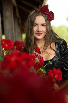 Beautiful girl, brunette in red corolla, surrounded by red flowers, portrait.