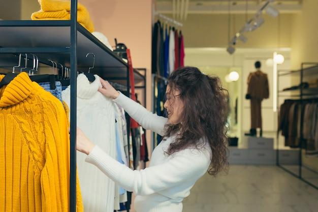 Красивая девушка покупатель примеряет и покупает красивую стильную одежду в бутике