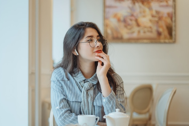 Beautiful girl in a cafe drinking tea