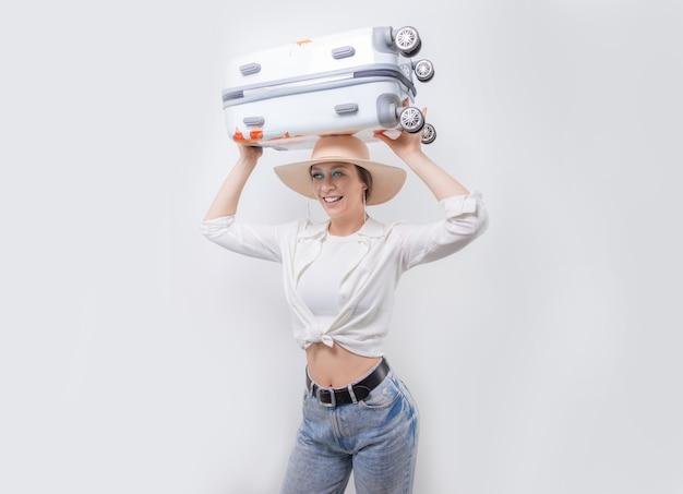 Красивая девушка несет чемодан на голове на белом фоне. концепция туризма. смешанная техника