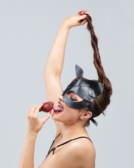 Beautiful girl in a cat mask. seductively posing with strawberries
