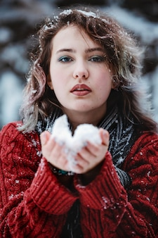 A beautiful girl of caucasian appearance in a burgundy sweater holds snow in her hands. winter day.