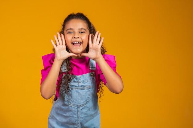 아름다운 소녀 아이는 노란색 스튜디오 배경 벽에 격리된 얼굴 근처에 손을 잡고 전화를 걸고, 감정적인 작고 예쁜 아이가 입을 벌리고 카메라 소리를 내며 큰 소리로 발표 개념을 말합니다.