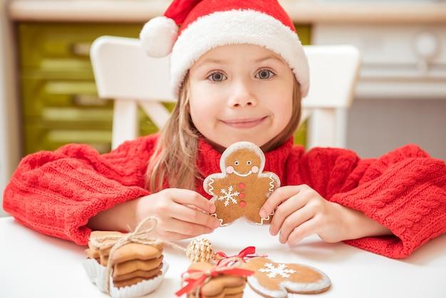Красивая девочка играет с имбирным печеньем