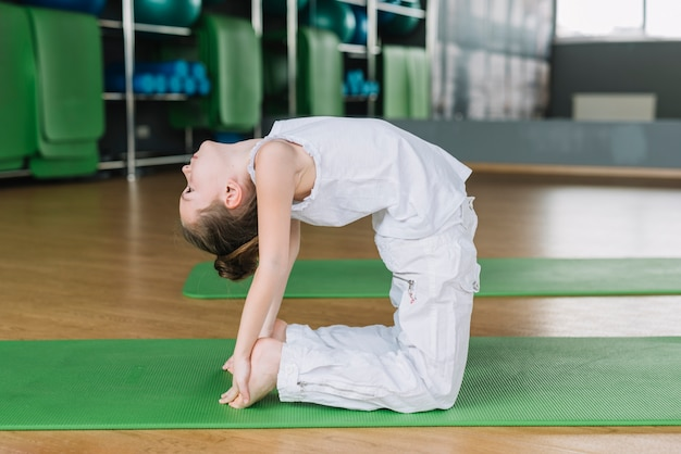 Beautiful girl child practicing camel pose in gym