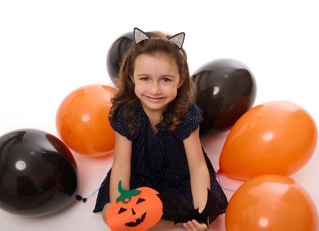 Красивая девочка улыбается с зубастой улыбкой, играя с самодельной тыквой из фетра на белом фоне с лежащими надутыми воздушными шарами черного и оранжевого цвета. концепция хэллоуина, копия пространства