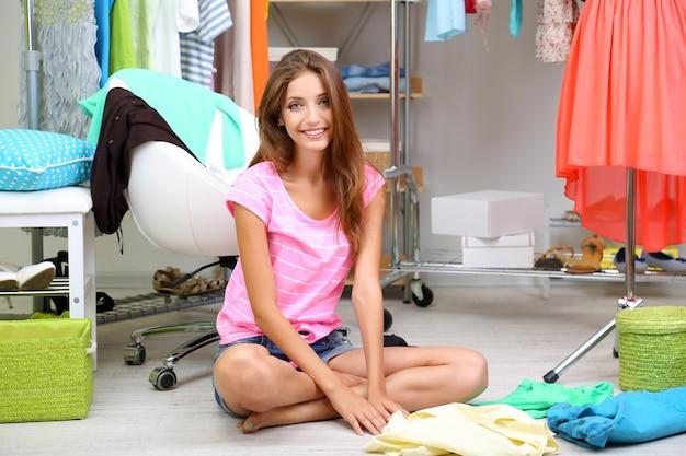 美しい少女がウォークインクローゼットで服を選ぶ