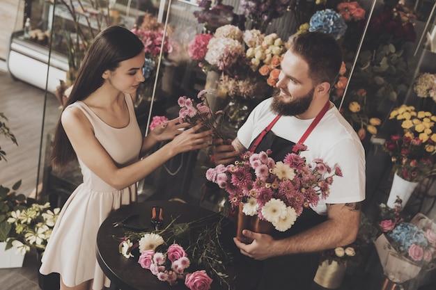 Beautiful girl chooses fresh flowers for gift