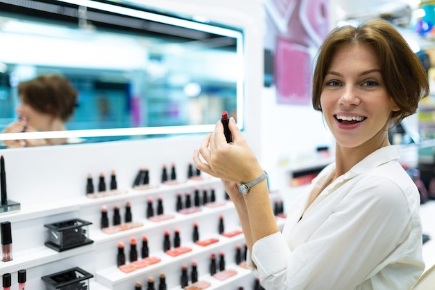 Beautiful girl chooses a lipstick in the store and thinks