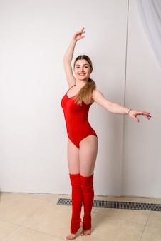 Beautiful girl choreographer in a red suit.
