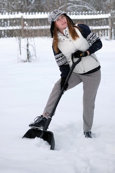 Beautiful girl cleans snow with a shovel.