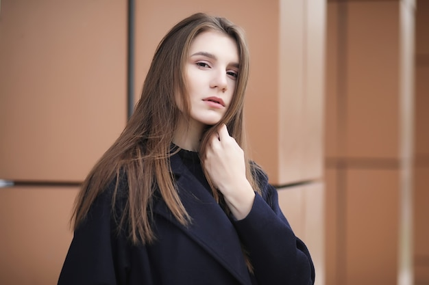 Beautiful girl in a coat in business downtown of the cloudy