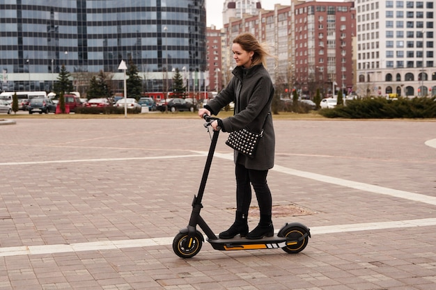 Beautiful girl in a coat rides electric scooter around the city