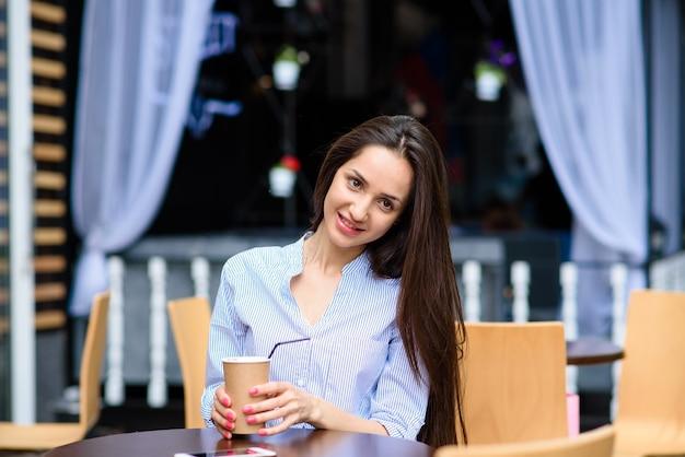 Красивые девушки пьющие кофе на улице