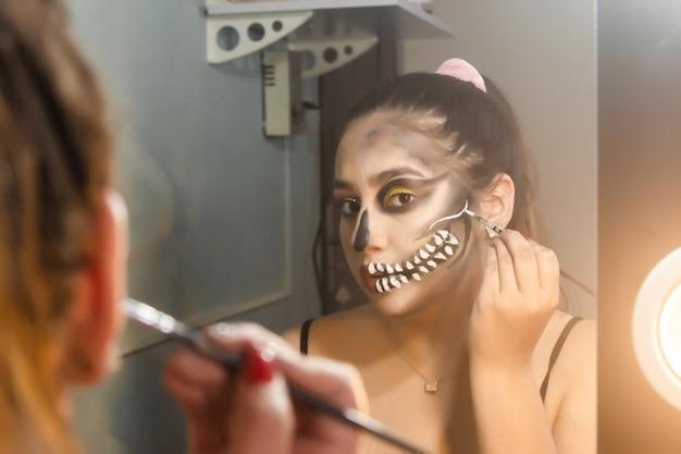 Красивая девушка концентрируется на создании художественного черепа для хэллоуина в своей комнате.