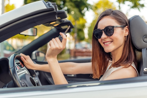 Beautiful girl in the  convertible cabrio car on a sunny day in a city