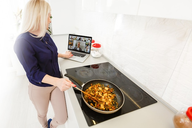 Beautiful girl  cook healthy food online by the internet from a laptop in gray kitchen on table.