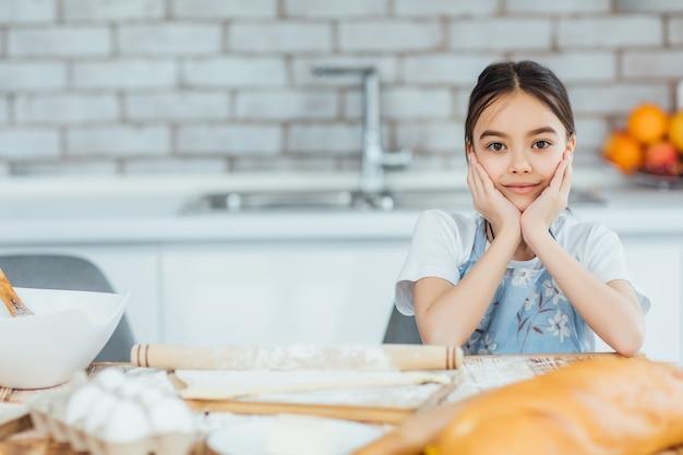 キッチンで料理をする美しい少女