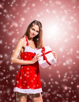 Beautiful girl in costume of santa claus with shopping at the christmas background