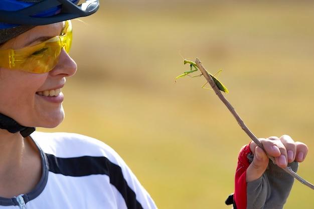 Велосипедист красивая девушка держит жука-богомола. природа и человек