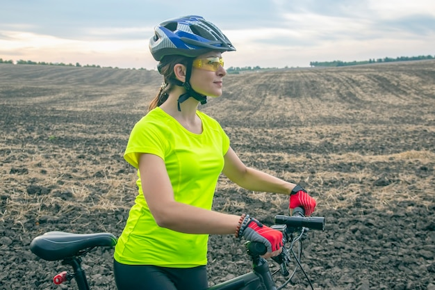 Beautiful girl cyclist rides a bicycle on the field. healthy lifestyle and sport. leisure and hobbies
