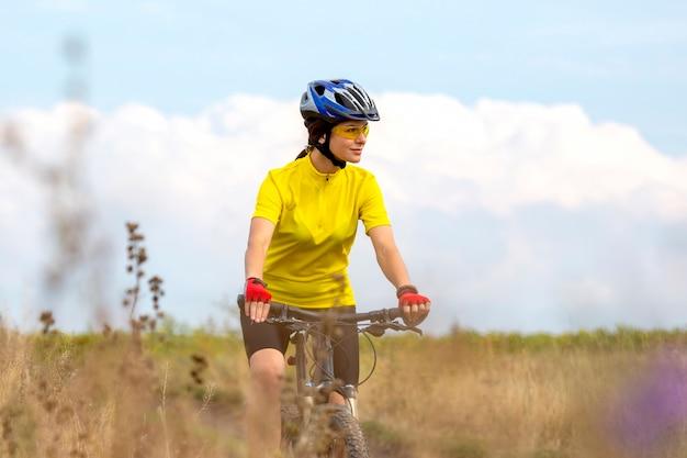 아름 다운 여자 사이클 자전거 필드에 타기. 건강한 라이프 스타일과 스포츠. 여가와 취미