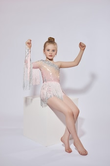 Beautiful girl in a dance dress on white sits on cube