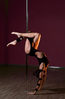 Beautiful girl dances near the pole.