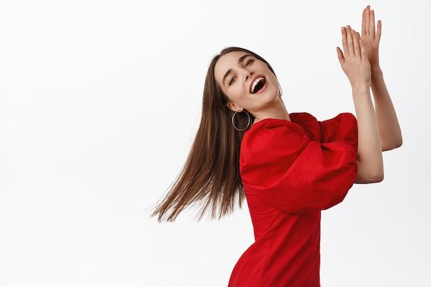 플라멩코를 추는 아름다운 소녀, 웃고 음악과 춤을 즐기고, 리듬에 맞춰 박수를 치며, 자연스럽게 웃고, 흰색에 빨간 드레스를 입고 포즈를 취합니다.