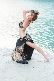 水の近くの白い砂浜で部族スタイルで踊る美しい少女