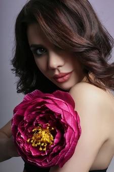 Beautiful girl dark hair and big flower near face