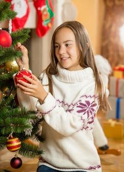 Beautiful girl decorating christmas tree at living room