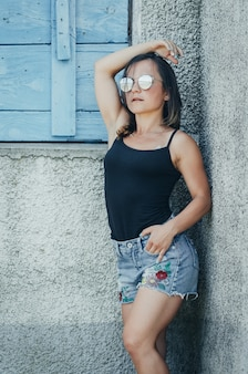 Beautiful girl in denim shorts and black tank top grunge style