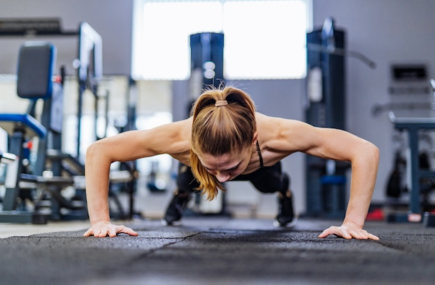 Beautiful girl does push-ups from the floor for training the muscles of the hands in the gym